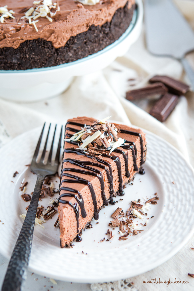 Easy No Bake Triple Chocolate Cheesecake with chocolate shavings and chocolate sauce