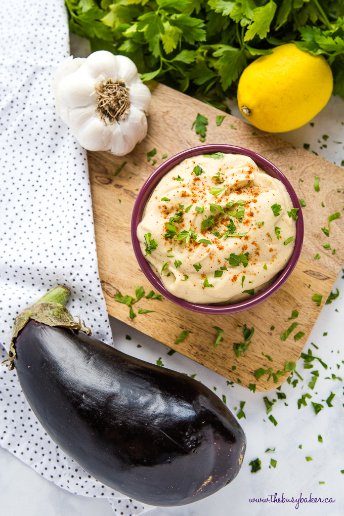 Easy Homemade Baba Ganoush in purple bowl with garlic, eggplant and fresh herbs