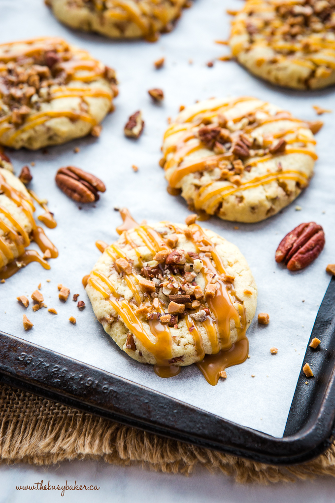 Caramel Butter Pecan Cookies on baking sheet with caramel sauce
