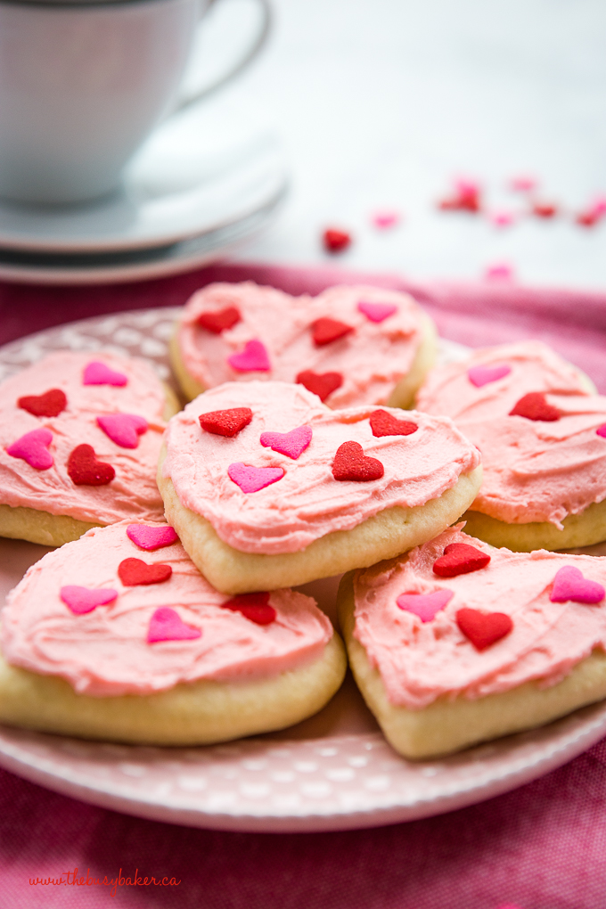 Classic Sour Cream Sugar Cookies with pink frosting and heart sprinkles