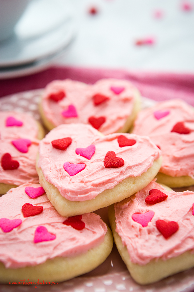 Classic Sour Cream Sugar Cookies on pink plate with heart sprinkles