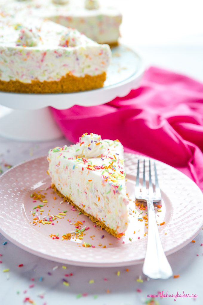 Easy No Bake Funfetti Cheesecake on pink plate with sprinkles