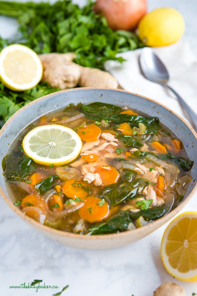 Crock Pot Lemon Ginger Chicken Soup in blue pottery bowl with fresh herbs and lemon slices
