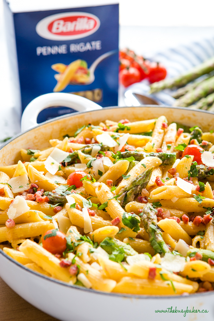Easy 20-Minute Tomato Asparagus Carbonara Pasta in white casserole dish with fresh veggies and bacon