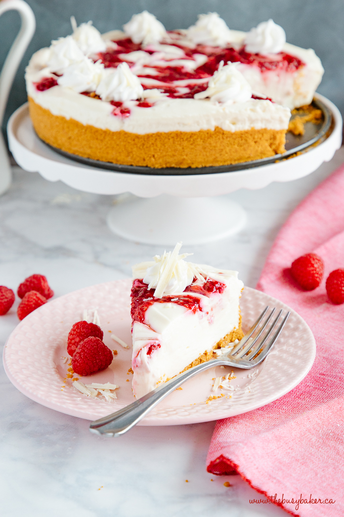 Easy No Bake White Chocolate Raspberry Cheesecake on pink plate with fork and fresh raspberries