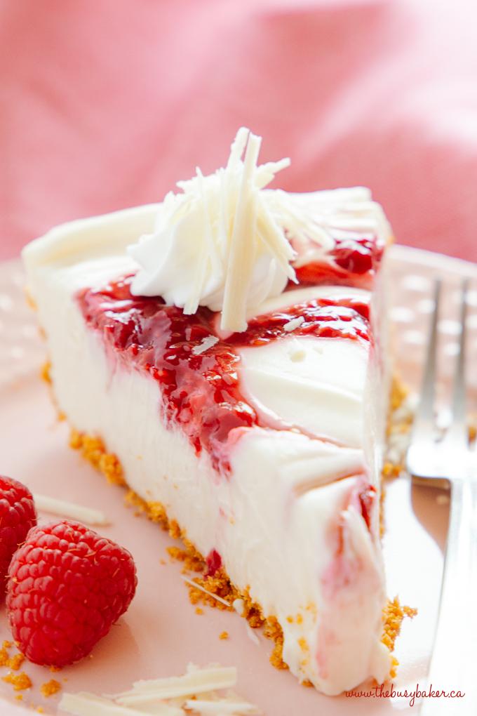 Easy No Bake White Chocolate Raspberry Cheesecake with raspberry swirls and fresh raspberries