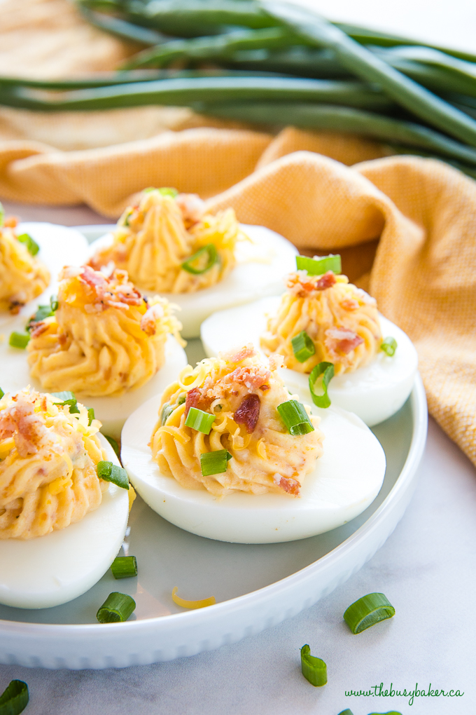 Best Ever Cheddar Bacon Ranch Deviled Eggs on blue plate with green onions