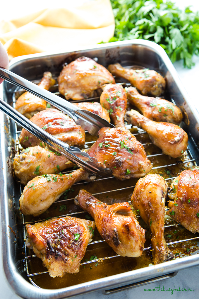 Maple Dijon Roasted Chicken with sticky glaze in roasting pan with fresh herbs