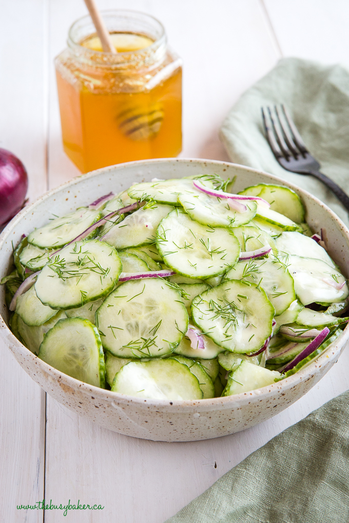 Cucumber salad with dill in pottery bowl