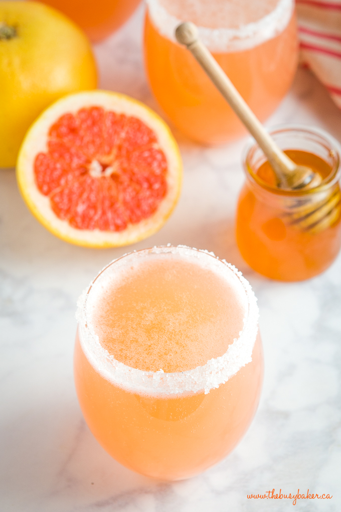 Pink grapefruit soda in glass with honey pot