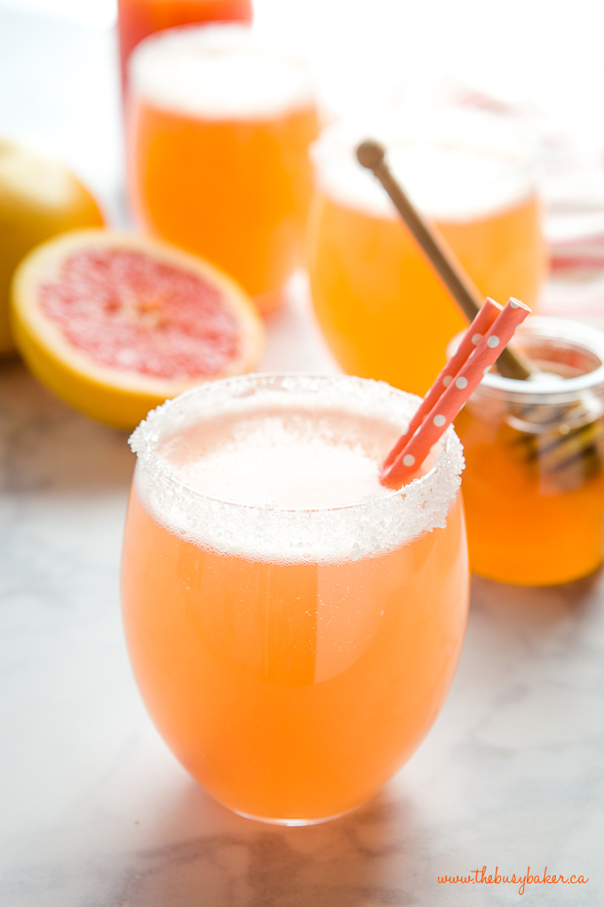 pink grapefruit soda in glass with paper straws