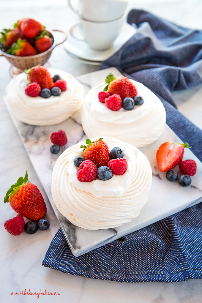 Meringue Nests with berries and vanilla whipped cream on marble slab