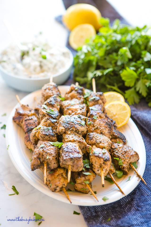 Plate of Greek pork souvlaki with lemon slices and herbs