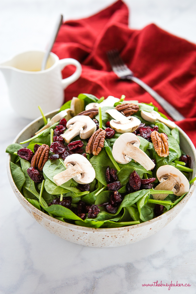 spinach salad in pottery bowl with cranberries and red napkin and fork