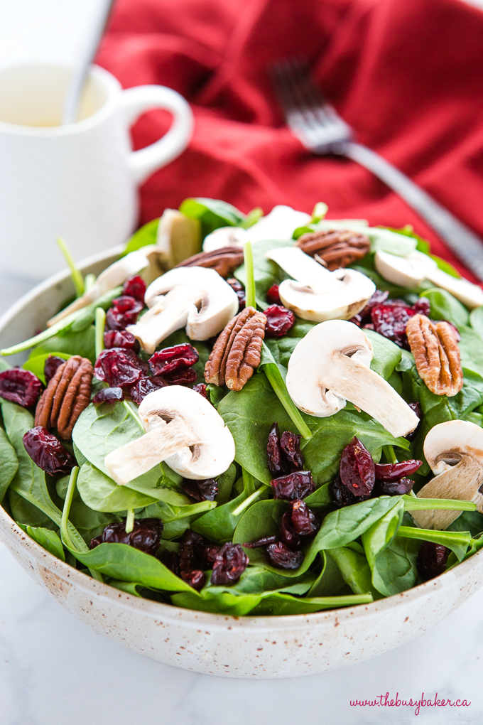 spinach salad with mushrooms and pecans with red napkin