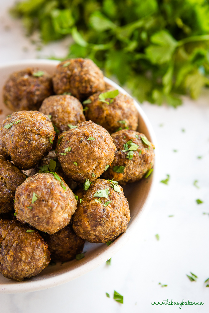 close up photo of meatballs in bowl with green herbs