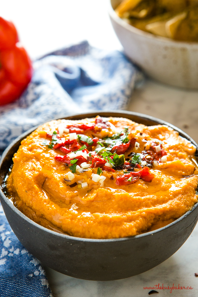 roasted red pepper hummus in black bowl with herbs
