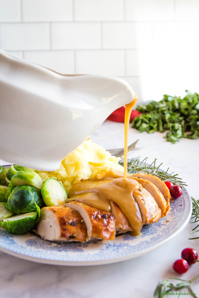 roast turkey gravy in white gravy boat, pouring on turkey breast