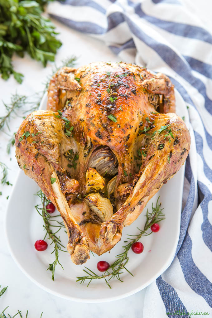whole roast turkey on white platter with cranberries and rosemary