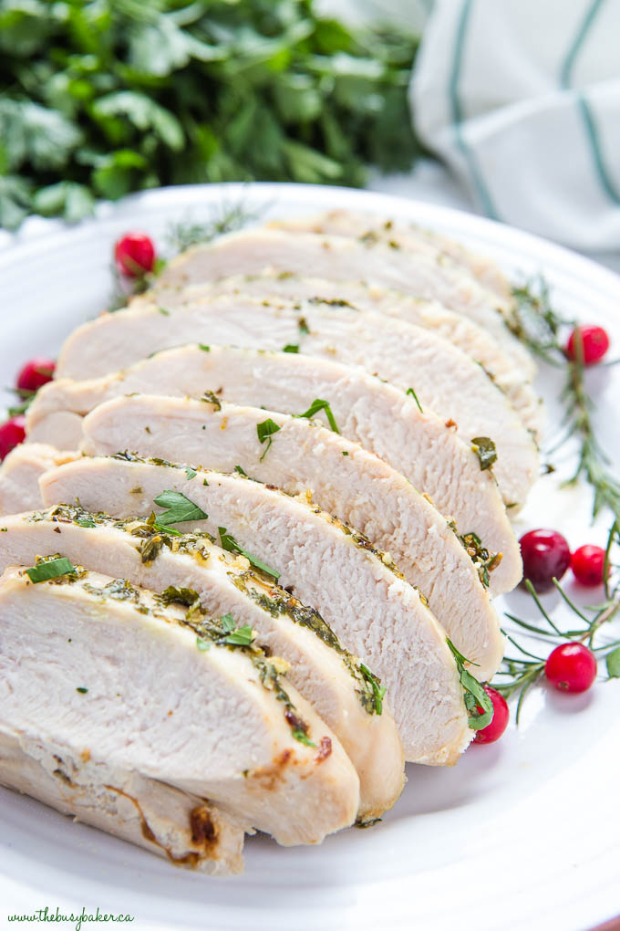 Sliced juicy roast turkey breast on white plate