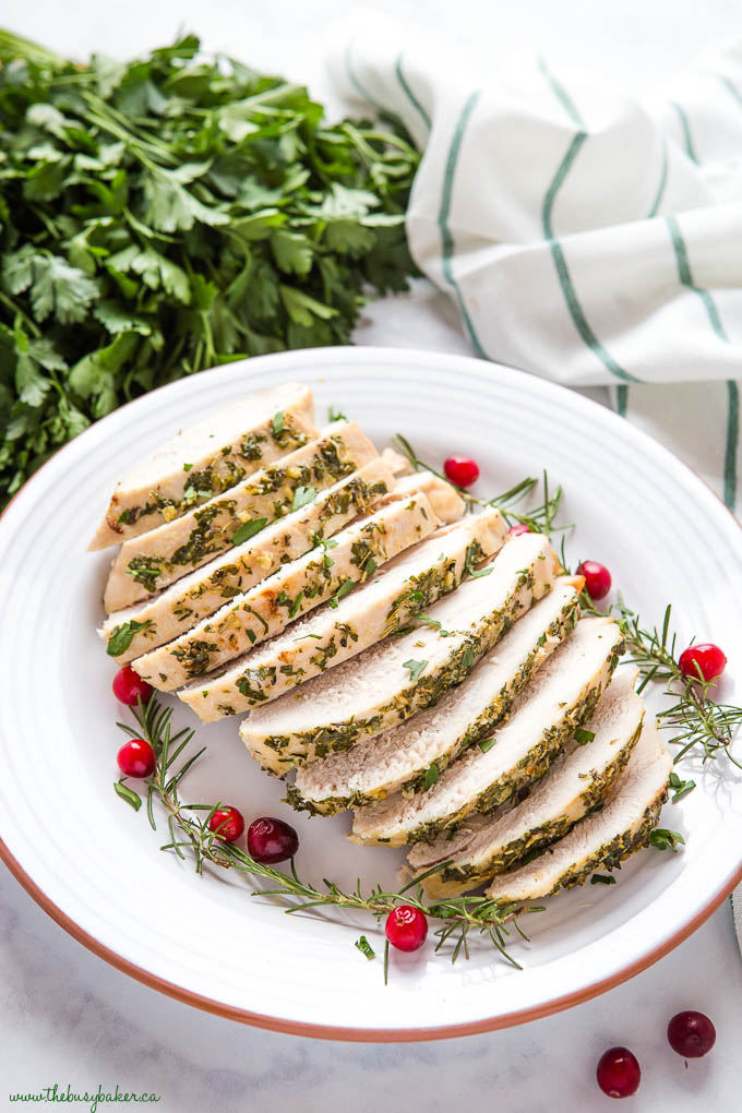Sliced roast turkey on plate with fresh herbs and cranberries