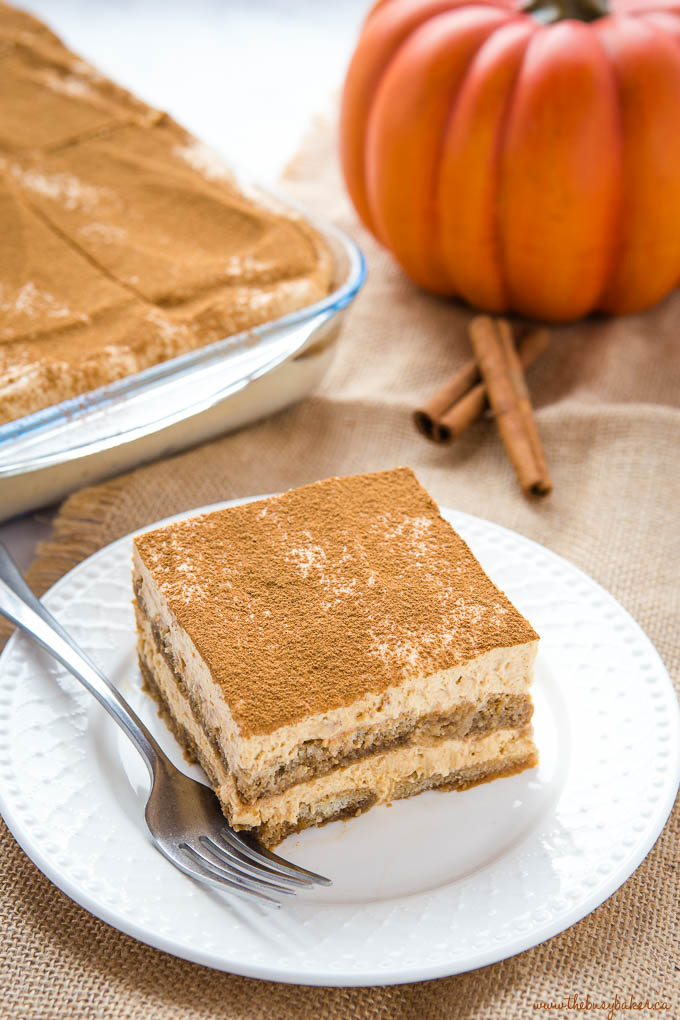 Layered pumpkin dessert on white plate with a fork