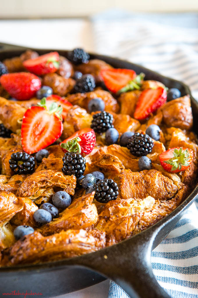 skillet croissant french toast casserole in cast iron skillet in fresh berries