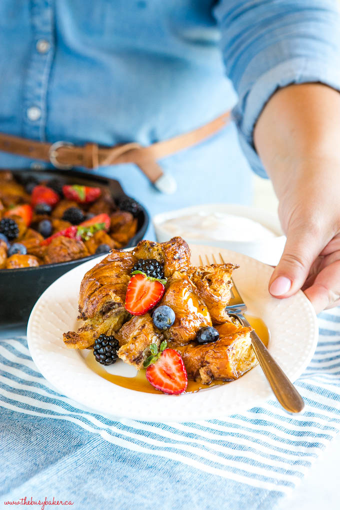 woman holding plate of skillet croissant french toast casserole