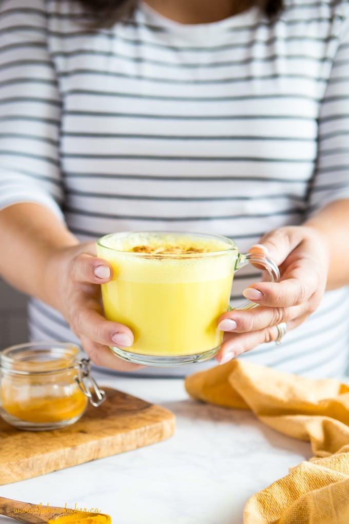 woman holding golden milk turmeric latte