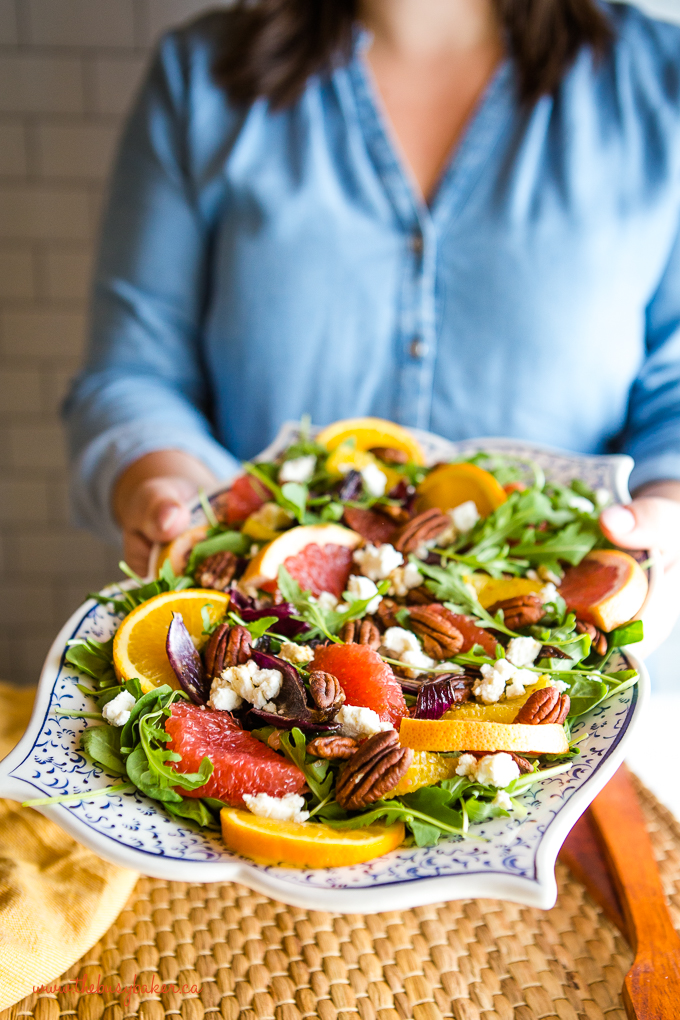 woman holding platter of winter citrus salad