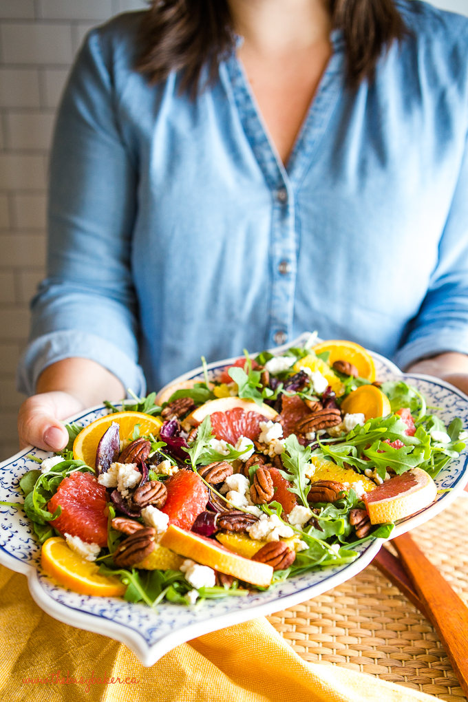 woman holding a platter of healthy spinach salad with fruit, nuts, and goat cheese