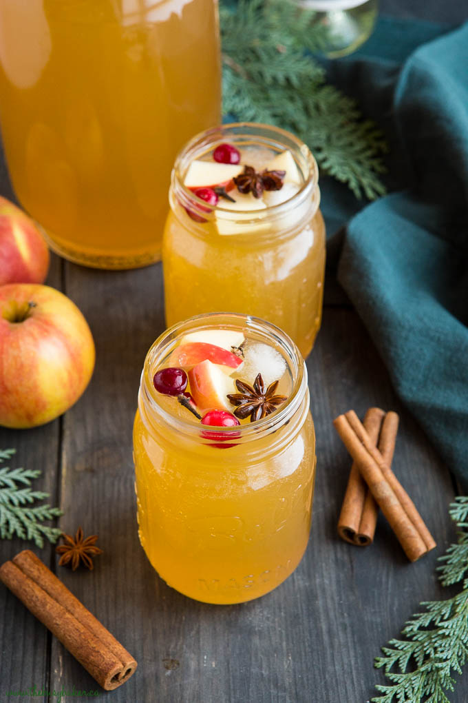 2 holiday cocktails made with apple cider and wine in mason jar glasses