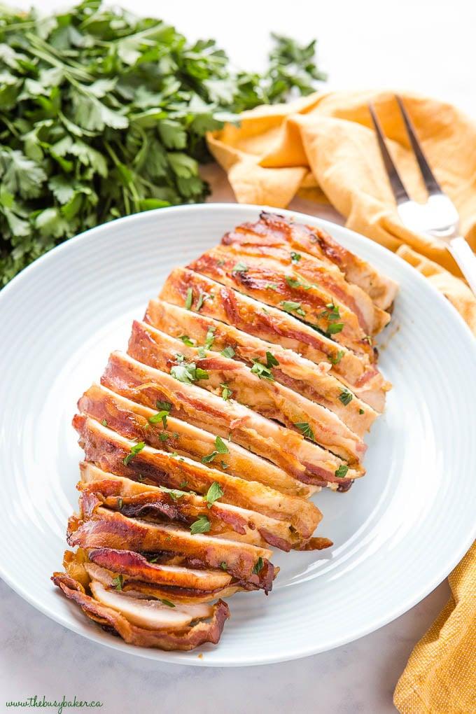 sliced roast turkey on blue plate with bacon