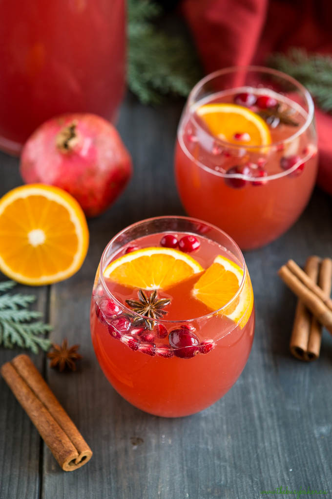 Christmas champagne punch in 2 clear drinking glasses garnished with oranges and star anise