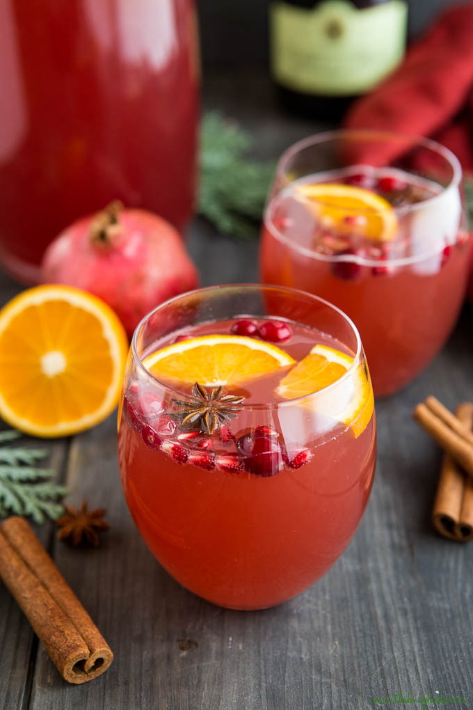 pink champagne cocktail in stemless glass garnished with citrus fruit and pomegranate arils