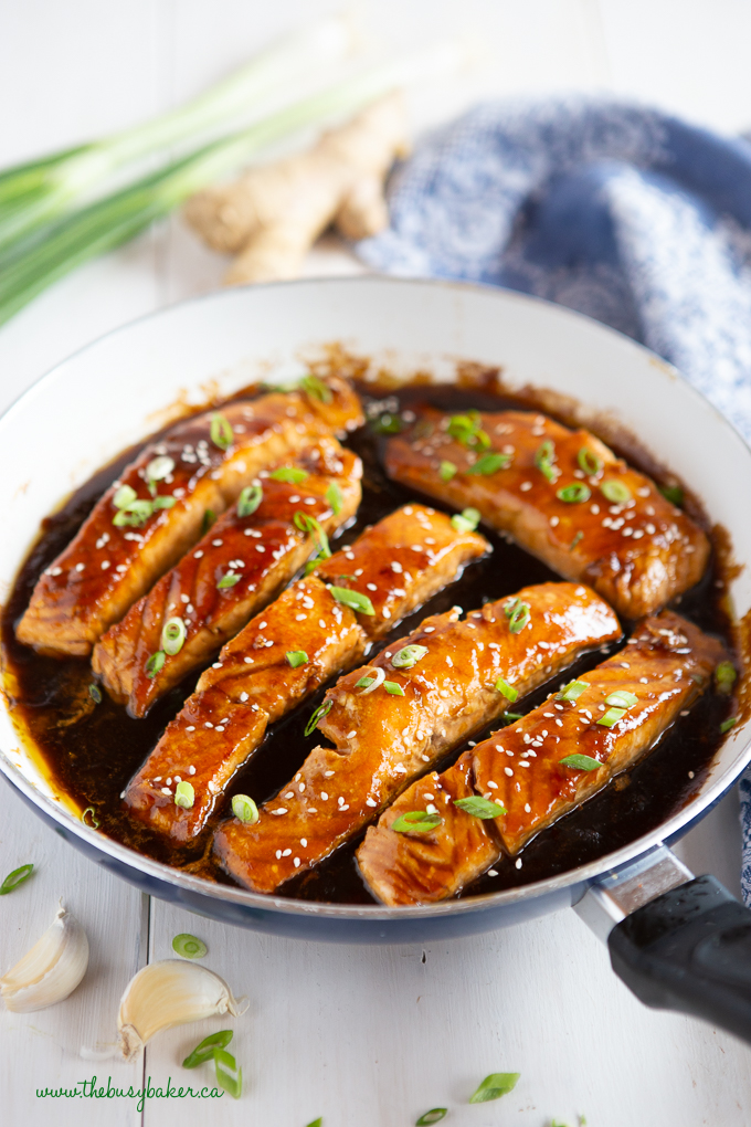 6 pieces of salmon cooking in a skillet with teriyaki sauce