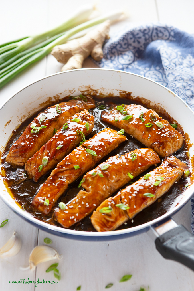 teriyaki glazed salmon topped with chives in white pan