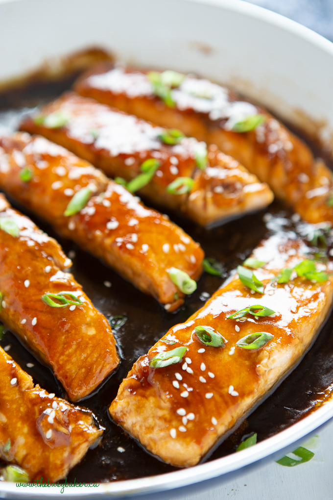 Glazed fish fillets with sesame seeds and scallions in dark sauce close up in white skillet