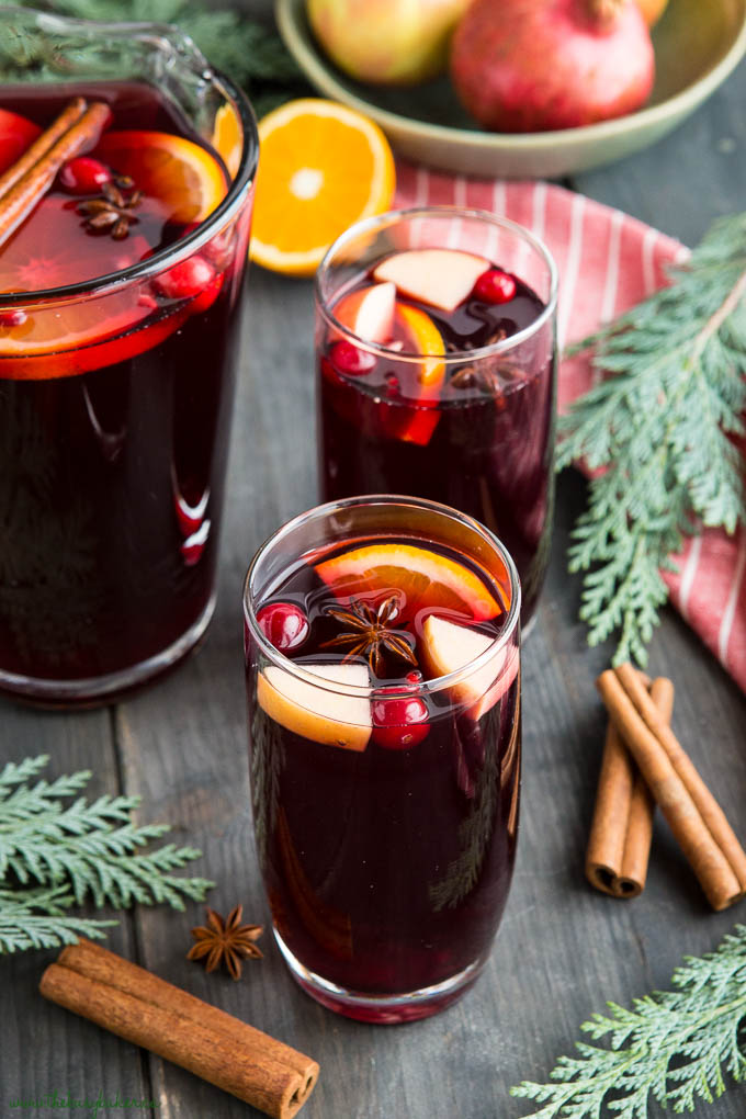 holiday sangria with orange slices and cranberries and cinnamon sticks