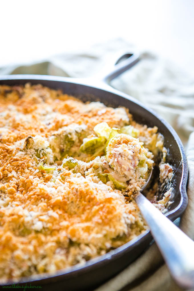 creamy Brussels Sprouts Gratin in cast iron pan with serving spoon