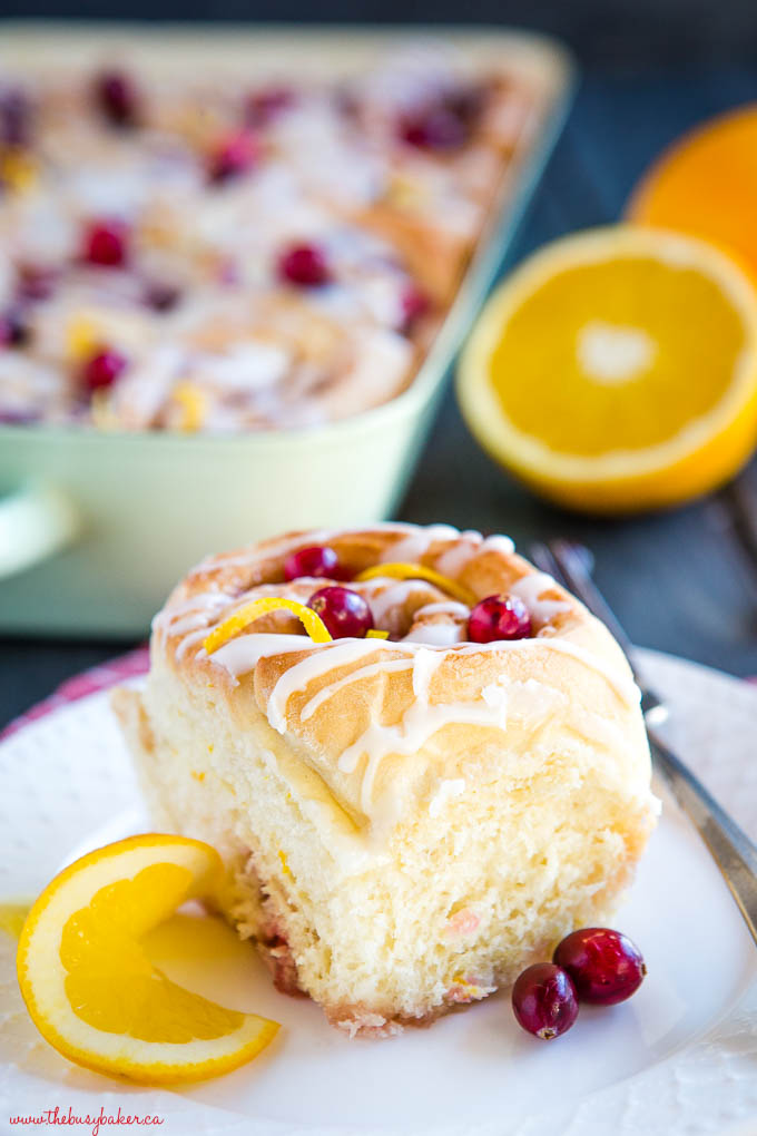 sweet roll on white plate with orange and cranberries