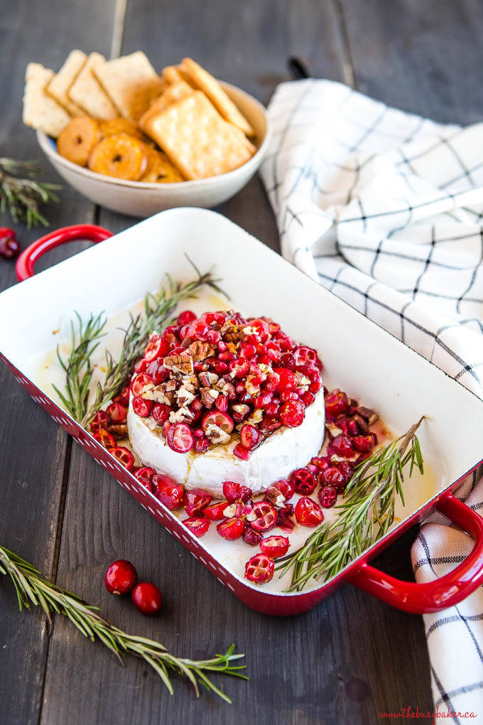 cranberry pomegranate baked brie in red pan with rosemary