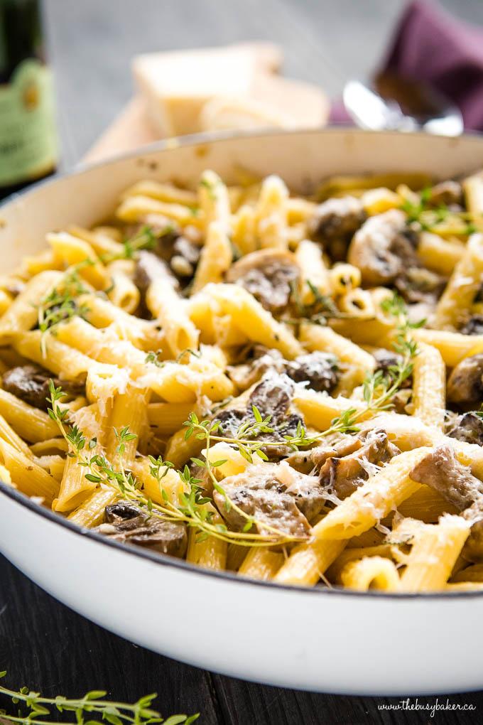 creamy mushroom pasta with fresh herbs in white pan