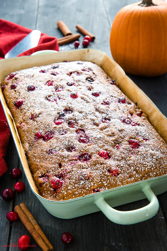 pumpkin cranberry cake with powdered sugar in green pan