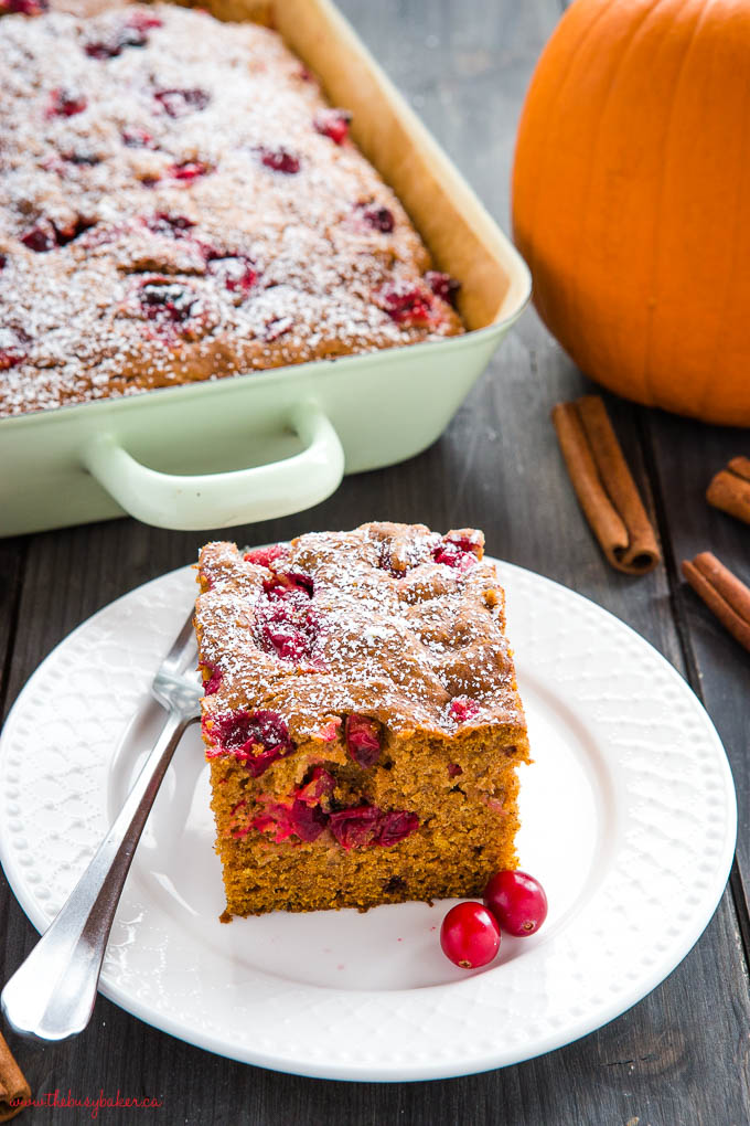 easy pumpkin cranberry cake, sliced on white plate with fresh cranberries and powdered sugar