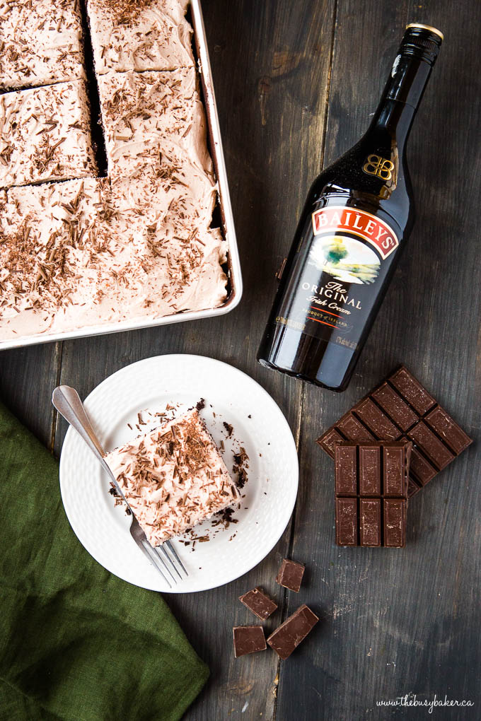 overhead photo: bottle of Bailey's Irish Cream next to a slice of cake with Bailey's frosting