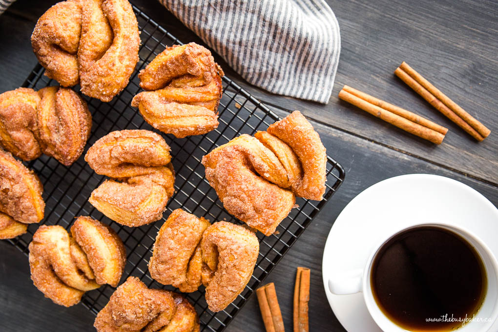 overhead photo: homemade cinnamon sugar twist donuts next to a cup of coffee