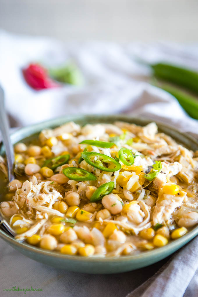 dairy free white chicken chili in green bowl with corn and jalapenos