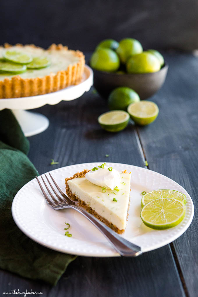 slice of key lime pie on white plate with fork and lime slices