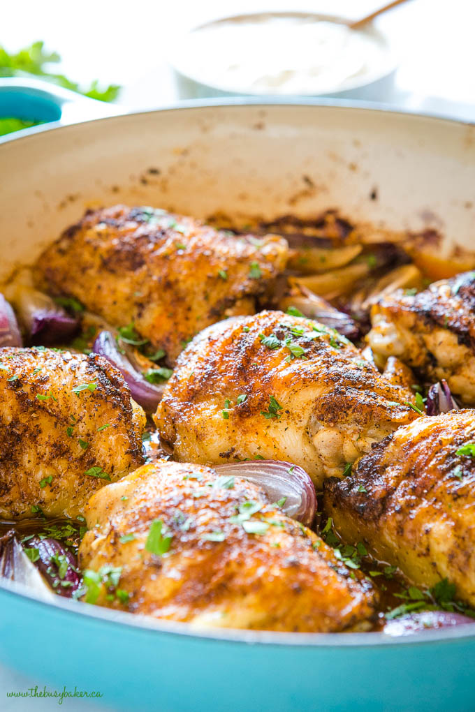roasted harissa chicken thighs in blue cast iron pan